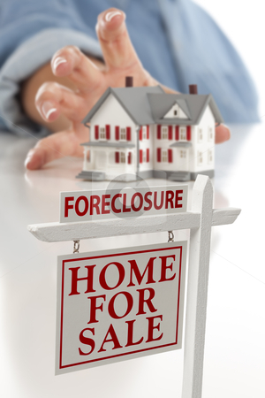 Foreclosure Sign in Front of Woman Reaching for House stock photo, Foreclosure Real Estate Sign in Front of Womans Hand Reaching for Model House on a White Surface. by Andy Dean