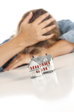 Woman with Head in Hand Behind Model Home stock photo, Woman with Head in Hand Behind Model Home on a White Surface. by Andy Dean