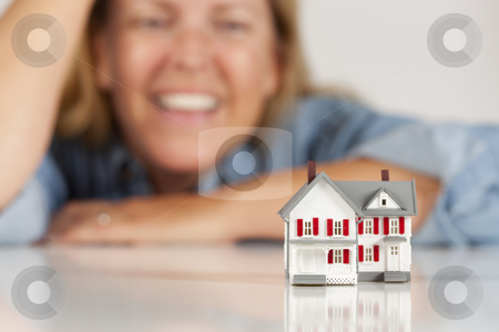 Smiling Woman Behind Model House on a White Surface stock photo, Smiling Woman Leaning on Hands Behind Model House on a White Surface. by Andy Dean