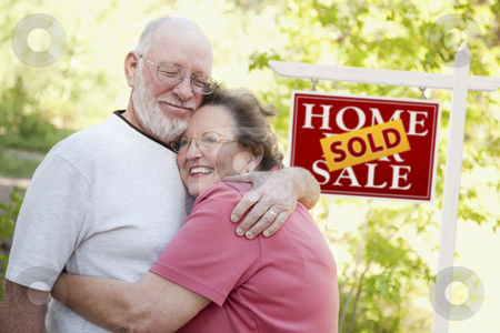 Senior Couple in Front of Sold Real Estate Sign stock photo, Happy Affectionate Senior Couple Hugging in Front of Sold Real Estate Sign. by Andy Dean