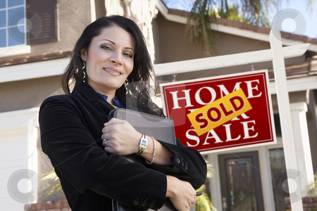 Hispanic Woman in Front of Real Estate Sign and New Home stock photo, Proud, Attractive Hispanic Woman in Front of Sold Real Estate Sign and New Home. by Andy Dean