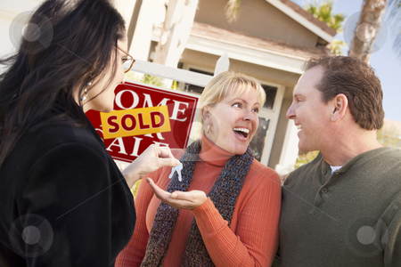 Hispanic Female Real Estate Agent Handing Keys to Excited Couple stock photo, Hispanic Female Real Estate Agent Handing Over New House Keys to Excited Couple. by Andy Dean
