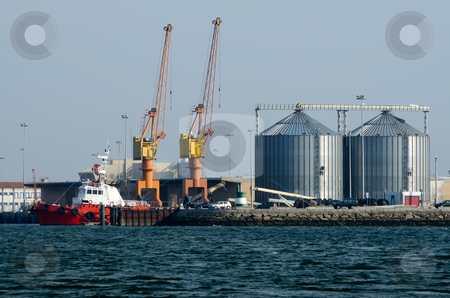 View on trading seaport stock photo, View on trading seaport with cranes and  red tug boat. by Homydesign