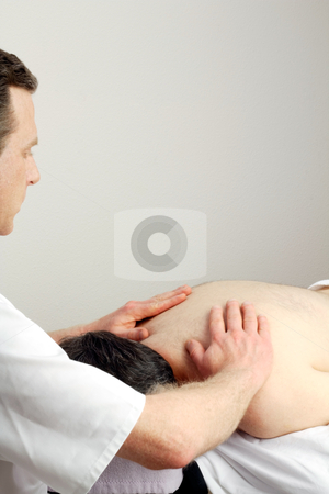Massaging Torso stock photo, Face down man receiving an upper back massage from a male massage therapist.  by Lee Serenethos