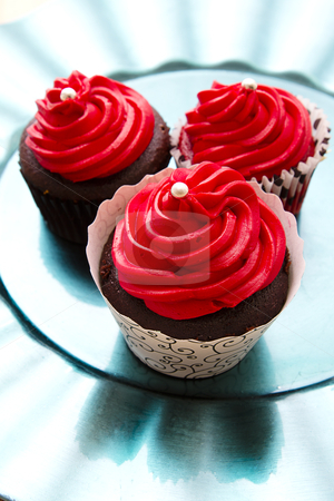 Fancy cupcakes stock photo, three chocolate cupcake with red icing a pearl on a turquoise plate by Yann Poirier