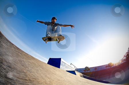 Skateboarder flying stock photo, Skateboarder flying over a ramp on sunset at the local skatepark. by Homydesign 