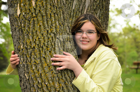 Tree Hugger stock photo, A smiling young girl is hugging a tree. by Richard Nelson