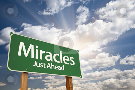 Miracles Green Road Sign Against Clouds stock photo, Miracles Green Road Sign Against Clouds and Sunburst. by Andy Dean