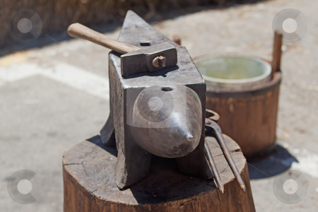 Hammer and anvil stock photo, Old hammer and anvil over a wooden block by Fabio Alcini