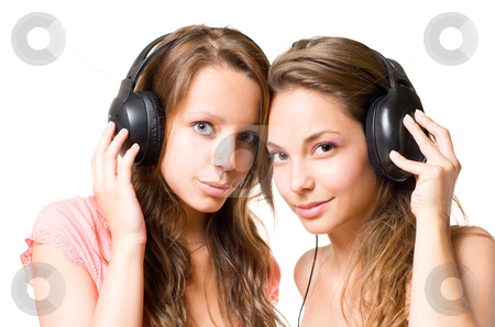 Our favorite tune. stock photo, Two beautiful young brunettes sharing their music playing in their headphones, isolated on white background by exvivo