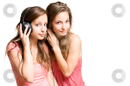 Sharing the same tune. stock photo, Two gorgeous young brunette girls sharing a tune in their headphones, isolated on white background. by exvivo