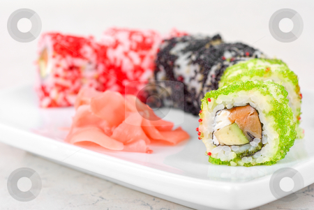 Sushi rolls stock photo, Sushi rolls made of fish avocado and different flying fish roe (tobiko caviar) by olinchuk