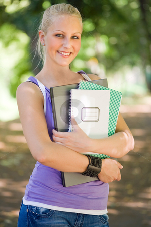 Young blond student girl portrait outdoors. stock photo, Outdoor portrait of beautiful young blond student girl holding exercise books and laptop. by exvivo