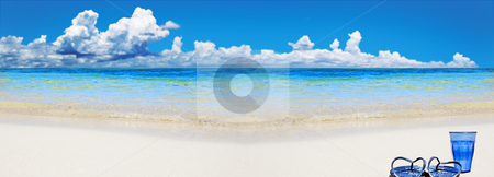 Tropical beach with beach shoes and glass of water stock photo, Tropical beach with beach shoes and blue glass of water by tish1