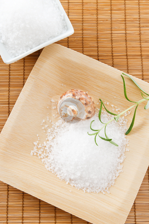 Bath salt scrub with aromatic rosemary stock photo, Overhead view of sea salt bath scrub arranged on a bamboo background with rosemary and a seashell. by Karen Sarraga