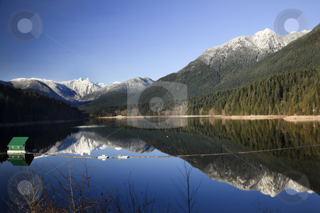 Capilano Reservoir Lake Snowy Two Lions Mountains Vancouver Brit stock photo, Capilano Reservoir Lake Long Reflection Green Building Dam Snowy Two Lions Snow Mountains Vancouver British Columbia Pacific Northwest by William Perry