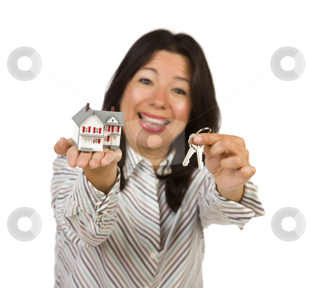Attractive Multiethnic Woman Holding Small House and Keys stock photo, Attractive Multiethnic Woman Holding Small House and Keys Isolated on a White Background - Focus is on the house and keys. by Andy Dean