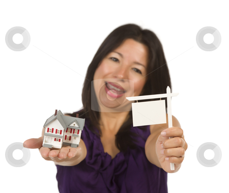 Multiethnic Woman Holding Small Blank Real Estate Sign and House stock photo, Multiethnic Woman Holding Small Blank Real Estate Sign and House in Hand Isolated on White Background - Ready for Your Own Message. by Andy Dean