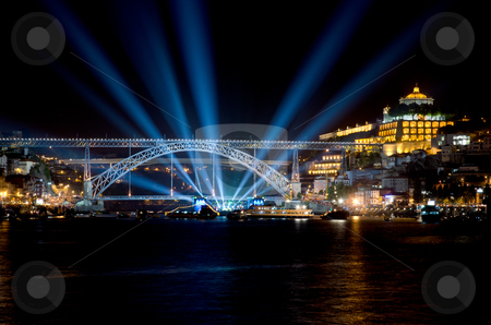 Dom Luis I bridge at night  stock photo, Dom Luis I bridge at night, during a music concert and blue light rays on the dark sky and boats on the water. by Homydesign