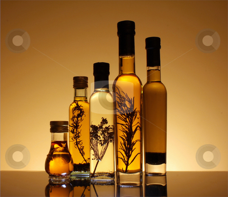 Collection of bottles of olive oil. stock photo, Collection of bottles of olive oil illuminated from behind and underneath the bottles. The botles has olive oil with peper, rosemary and other seasonings. by marphotography