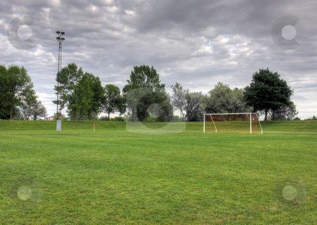 Overcast Soccer Field stock photo, A cloudy unoccupied soccer field with trees in the background. (HDR photograph)  by Chris Hill