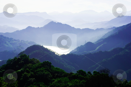 Lake surface reflect sunshine stock photo, mountains surround lake with light fog. The lake surface reflect sunshine. by Lawren