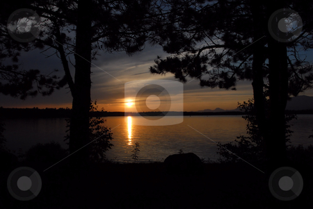 THrough the trees stock photo, Sunset over Lake Millinocket in Maine. Framed by two trees by Tim Markley