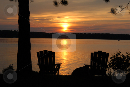 Chairs at sunset stock photo, Sunset over Lake Millinocket in Maine with two chairs for viewing. by Tim Markley
