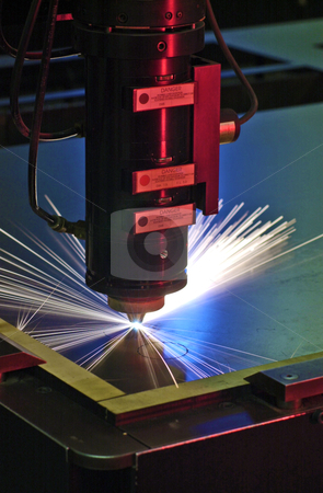 Industrial laser stock photo, Industrial laser cutter with blue and red background, with sparks  by Christian Delbert