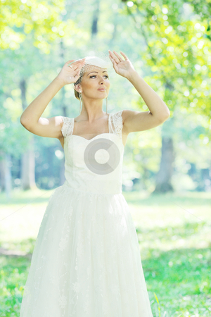 Beautiful bride outdoor stock photo, beautiful bride woman people in fashion wedding dress posing outdoor in bright park by Benis Arapovic