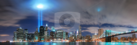 New York City Manhattan panorama  stock photo, Remember September 11. New York City Manhattan panorama view with Brooklyn Bridge at night with office building skyscrapers skyline illuminated over Hudson River and two light beam in memory of September 11. by rabbit75_cut