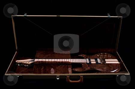 Exotic Wood Electric Guitar stock photo, A new electric guitar made of beautiful exotic wood sitting in it's case. by Robby Ticknor
