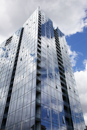 Tall modern reflecting building stock photo, Tall glass covered reflecting skyscraper with blue sky and clouds by bobkeenan