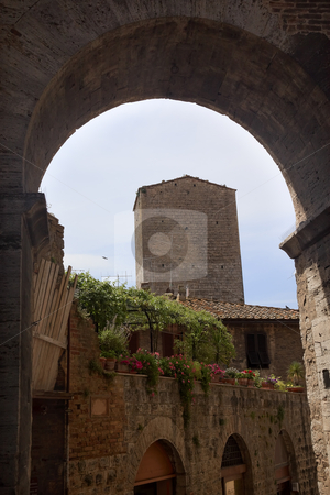 Medieval Arch Stone Tower Medieval Town San Gimignano Tuscany It stock photo, Medieval Arch Stone Tower Medieval Town Pink Flowers San Gimignano Tuscany Italy by William Perry
