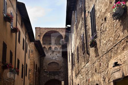 Arch Narrow Street Via San Giovanni San Gimignano Tuscany Italy stock photo, Arch Narrow Stone Streets Flowers Medieval Castle Town Via San Giovani San Gimignano Tuscany Italy by William Perry