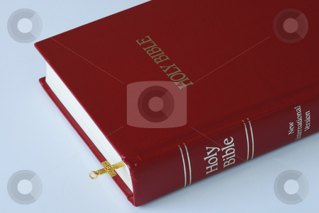 Using a golden cross as a bookmark for the bible stock photo, Using a golden cross as a bookmark for the bible by johnkwan