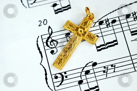 A golden cross on the top of a music sheet stock photo, A golden cross on the top of a music sheet by johnkwan