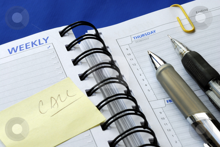 Write some notes on the day planner isolated on blue stock photo, Write some notes on the day planner isolated on blue by johnkwan