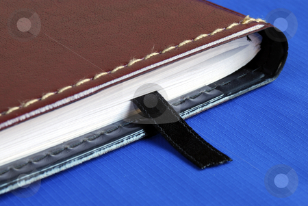 Brown notebook with a black bookmark isolated on blue stock photo, Brown notebook with a black bookmark isolated on blue by johnkwan