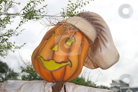 Pumpkin with jack o'latern face scarecrow stock photo, A pumpkin with a funny face and hat by Lucy Clark