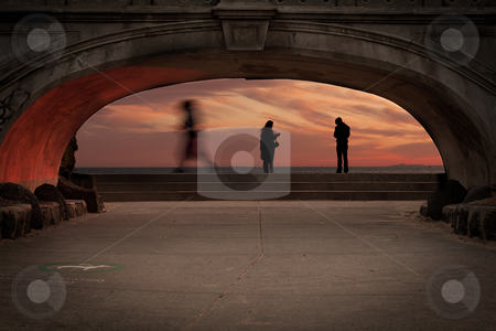 Beach Bridge stock photo, A beach side foot bridge with people walking in the background by HughAdams
