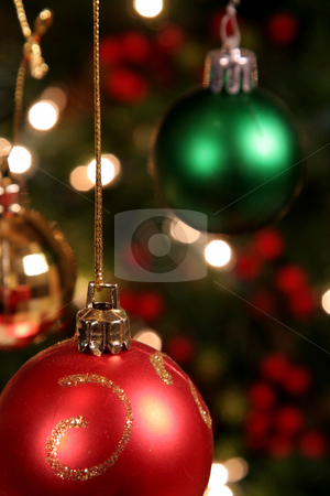 Three Xmas Baubles stock photo, Three Xmas Baubles shot in front of a Christmas Tree.  by Chris Hill
