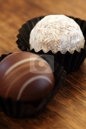 Two chocolate truffles stock photo, Photo of two chocolate truffles in paper wrappers.  Very Shallow depth of field, focusing on white truffle. by © Ron Sumners