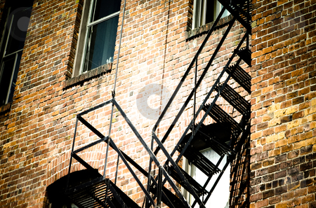 Fire escape stairs stock photo, an old bricks building and black fire escape stairs by Anatoliy Nykilchyk