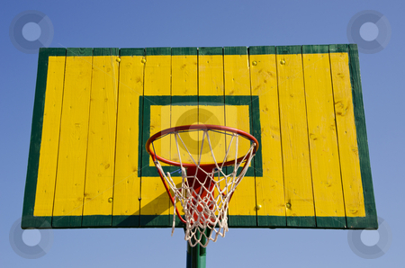 Basketball board stock photo, Basketball board painted green and yellow with net on the hoop. by sauletas