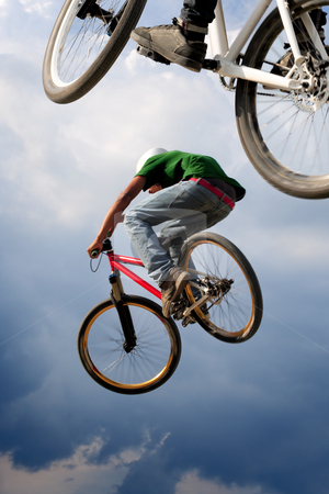 Airborne bikes stock photo, Two BMX bikers high up in the air.  Some motion blur on both bikers. by © Ron Sumners