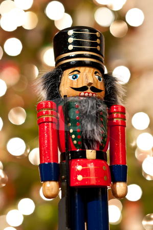 Nutcracker in Front of a Christmas Tree stock photo, A shiny wooden nutcracker stands in front of an out of focus Christmas tree. by Brian Guest