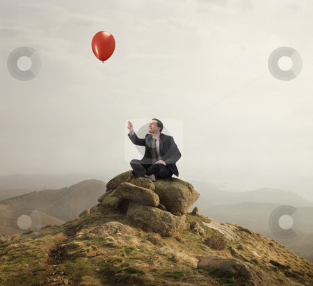 Freedom stock photo, Businessman sitting on a rock and holding a balloon by olly4