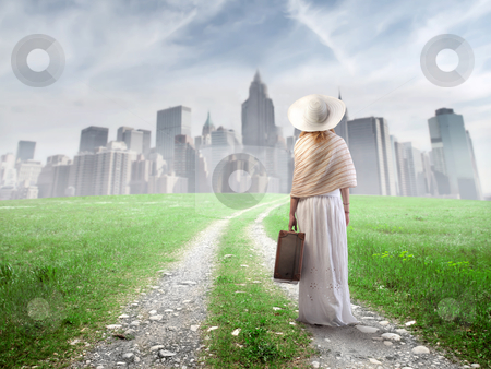Move stock photo, Young woman walking towards a big city with a suitcase in her hand by olly4
