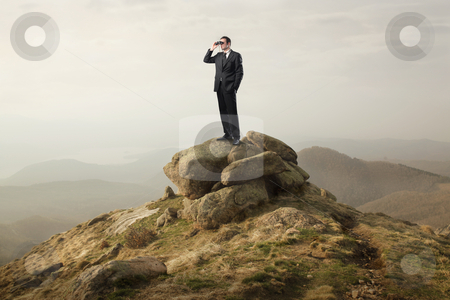 Progress stock photo, Businessman standing on a rock and using binoculars by olly4